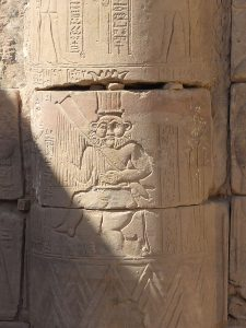 Bes playing harp on a column of Hathor temple, Philae Island, Egypt