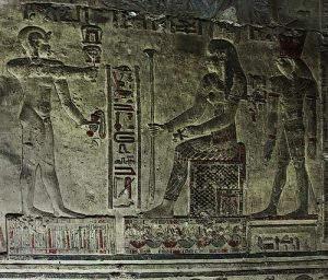 Ihy shaking a sistrum at Hathor while holding the menat. Horus looks on